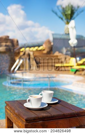 Two cups of coffee on the table near the pool.