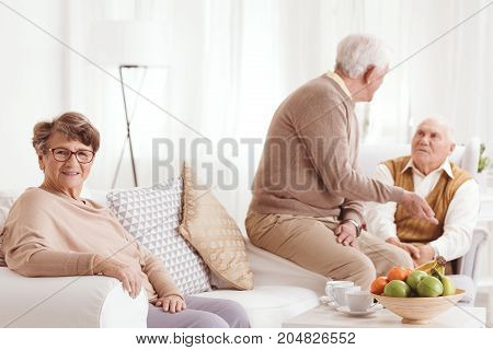 Group of older people drinking tea together at white living room