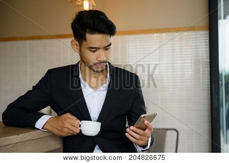 Businessman Using Smartphone During Coffee Time