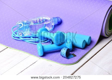 Barbells And Skipping Rope Next To Water Bottle On Mat