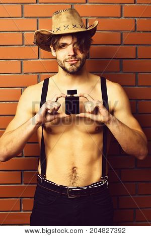 Caucasian Bearded Sexy Macho Man In Cowboy Hat Holding Perfume