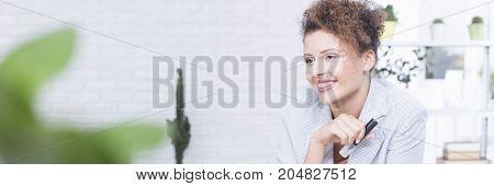 Smiling successful businesswoman in bright industrial interior