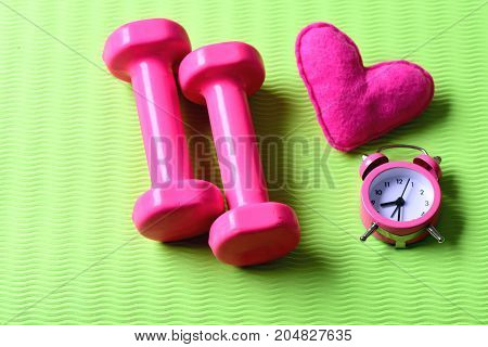 Dumbbells In Pink Color Next To Alarm Clock And Heart