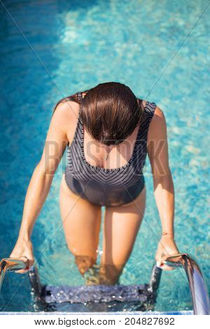 Showy girl coming out of a beautiful pool.
