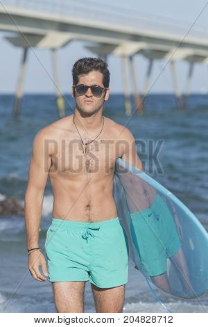 Young Attractive Surfer Holding His Surfboard At The Beach