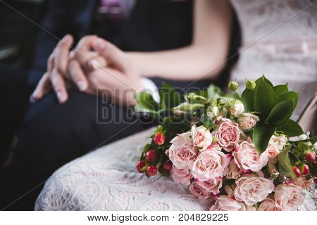 bride holding a wedding bouquet in the car