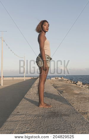 African American Woman Standup In Shorts On Beach