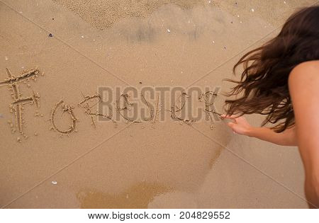The girl is writing an inscription on the sand-forever.