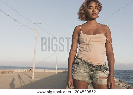 African American woman standup in shorts at Barcelona Beach