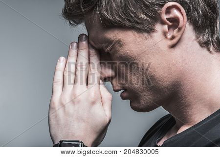 Close up of profile face of young guy concentrating on difficult question. He is touching forehead by hand with desperation and closed eyes. Isolated