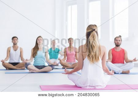 Yoga instructor is showing lotus position in white studio