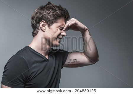 Side view of frustrated young man suffering from headache. He is touching eye area near nose with deep pain. Isolated and copy space