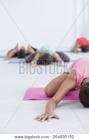 Practitioner is concentrating on yoga exercise while lying on pink mat