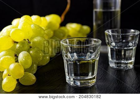 Two glasses and bottle of traditional drink Ouzo or Raki on black dish with a branch of grapes