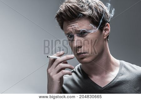 Portrait of pensive young man smoking cigarette. Smoke is near his eyes. Isolated and copy space