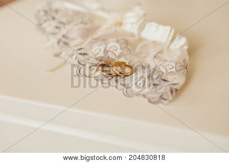 Golden wedding rings laying on lace garter on a white table. Wedding preparation. Artwork. Soft focus