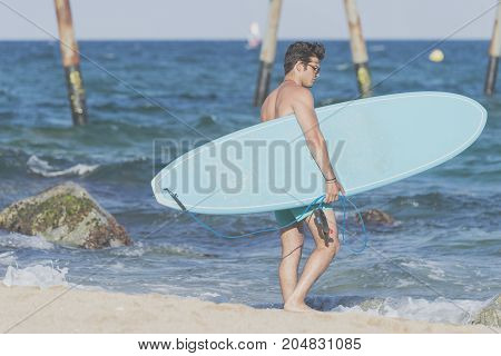 Surfer Carrying His Blue Surfboard From Behind