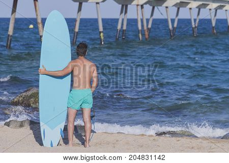 Surfer Holding His Blue Surfboard ( From Behind )