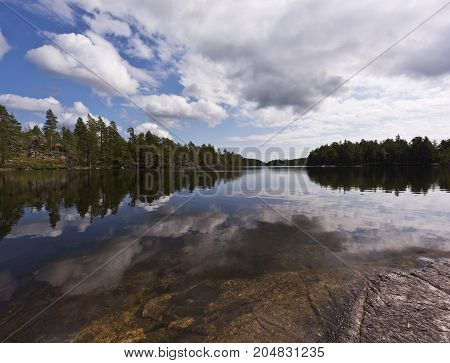 The summer landscape with a lake a forest and the sky. Sweden