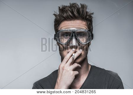 Scared young man is smoking while wearing protective mask on eyes. Smoking is dangerous concept. Isolated and copy space. Portrait