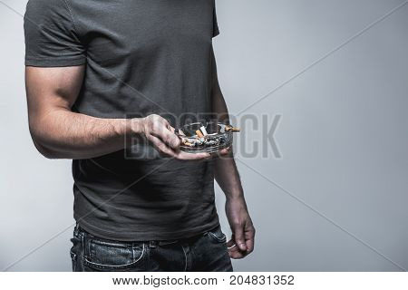 Close up of body of young man keeping ash-pot with tobacco stubs in arm. He is standing. Nicotine addiction concept. Isolated and copy space