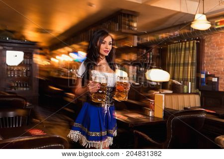 Beautiful female waitress wearing traditional dirndl and holding huge beers in a pub. Sexy brunette carries two glasses of beer between the tables in the bar