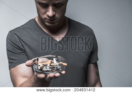 Pensive young man is looking at ashtray with lots of cigarette butts with sadness. He realizes his nicotine addiction. Focus on stubs. Isolated