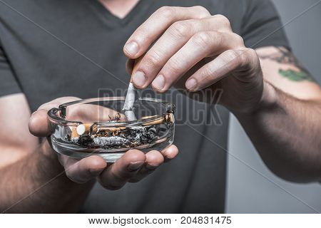 It is time to stop smoking. Close up of heavy smoker hand stewing cigarette in ashtray. Focus on other stubs