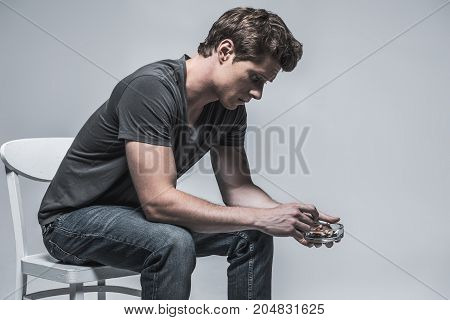 Pensive young man is holding burning cigarette under ashtray while looking inside with sadness. He is sitting on chair. Isolated and copy space