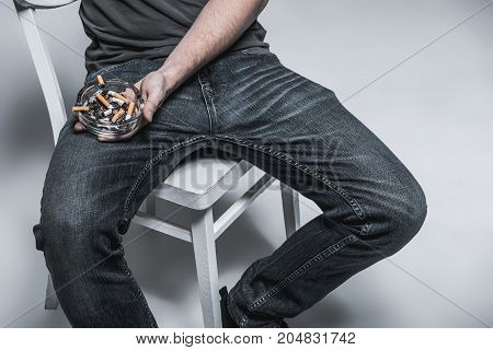 Close up of male hand holding ashtray with stubs on leg jeans. Man is sitting on chair