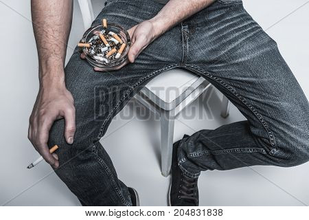 Top view close up of young man arm holding ashtray near his legs while sitting on chair. He is keeping burning cigarette in other hand