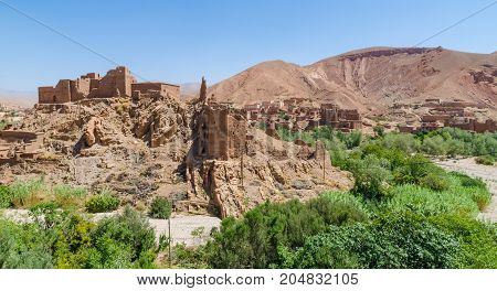 Old Moroccan clay kasbah perched on hill in Atlas mountains, Morocco, North Africa.