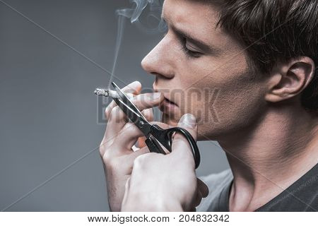 Profile of serious heavy smoker quitting bad habit. He is cutting cigarette by scissors with confidence. Isolated and copy space
