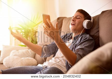Teenage Singing From Her Cellphone Sitting On Couch At Home