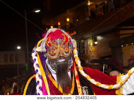 Quito, Ecuador - february 02, 2016: An unidentified man dressed up participating in the Diablada, with a mask in his head.