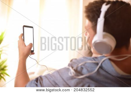 Teenager Looking At A Mobile And Listening To Music Behind