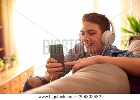 Teenager Watching Multimedia Content Leaning On The Back Of Couch