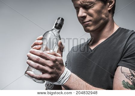 Drunk young man is suffering from alcohol addiction. He is standing and holding bottle. His eyes are closed with desperation and hands are tied. Isolated