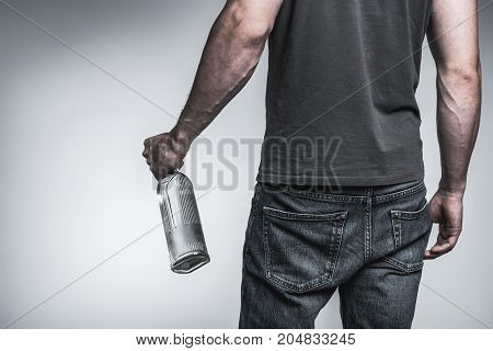 Close up of young man holding bottle of transparent alcohol beverage. Focus on his back. Isolated and copy space