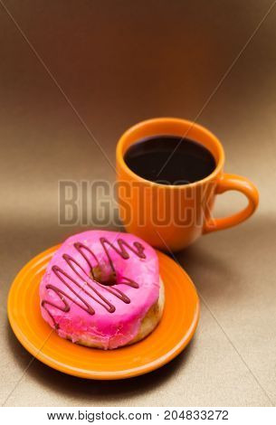 Delicious donut with pink glazed over an orange plate, with an orange cup of coffee in a soft brown background top view.