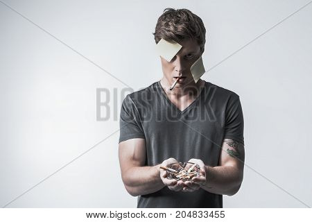 Having social label of heavy smoker. Irritated young guy is showing ashtray with lots of cigarette stubs. He is standing with stickers on face. Isolated and copy space