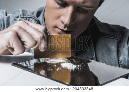 Depressed male junkie is dividing snow on lines by credit card with concentration. Focus on narcotic on mirror