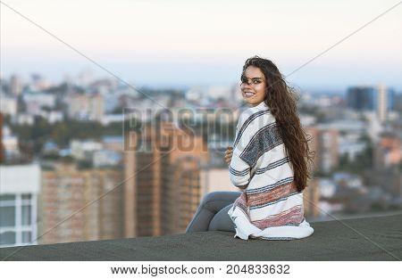 Young woman outdoors on city background in sunny day