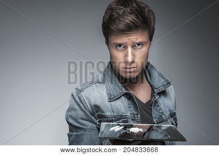 Portrait of sad young man holding mirror with white cocaine on it. He is standing and looking at camera with desperation. Narcotic addiction concept. Isolated and copy space