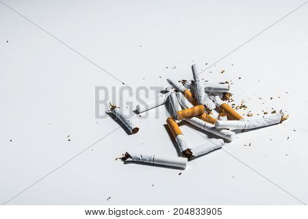 Close up of crushed cigarettes on white desk. Copy space in left side. Stop smoking concept