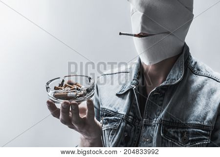 Nicotine kills your individuality. Young unrecognizable man is standing and keeping cigarette in mouth. He is holding ashtray with stubs while having wrapped face. Isolated and copy space