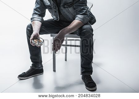 Close up of male body sitting on chair and holding ashtray with cigarette butts. Isolated and copy space