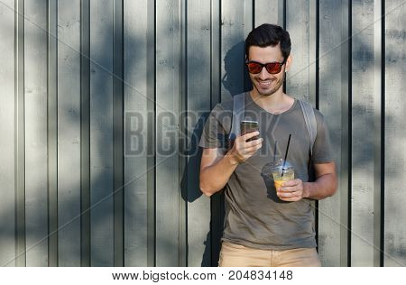 Horizontal Outdoor Image Of Young Optimistic European Man Pictured With Grey Wooden Fence Behind, Lo