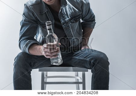 Close up of male body holding bottle of alcohol beverage. Man is sitting on chair. Isolated
