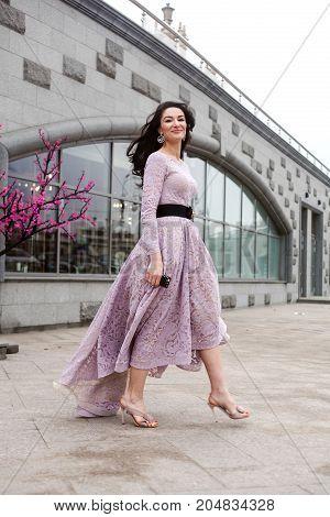 beautiful brunette female in long pink dress walking in the street